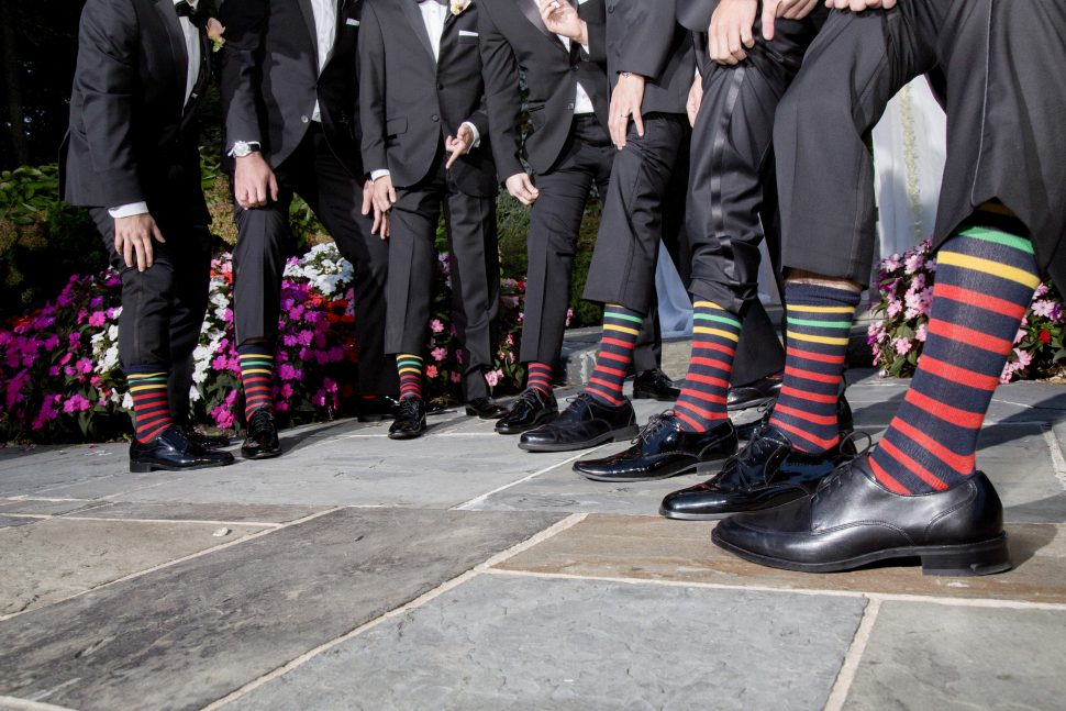Groomsmen at a wedding showing off their matching colorful socks