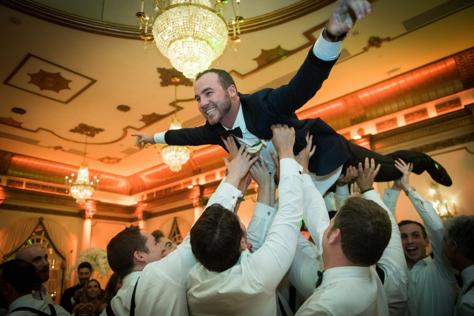 The groom is held up by his groomsmen, as though flying through the air