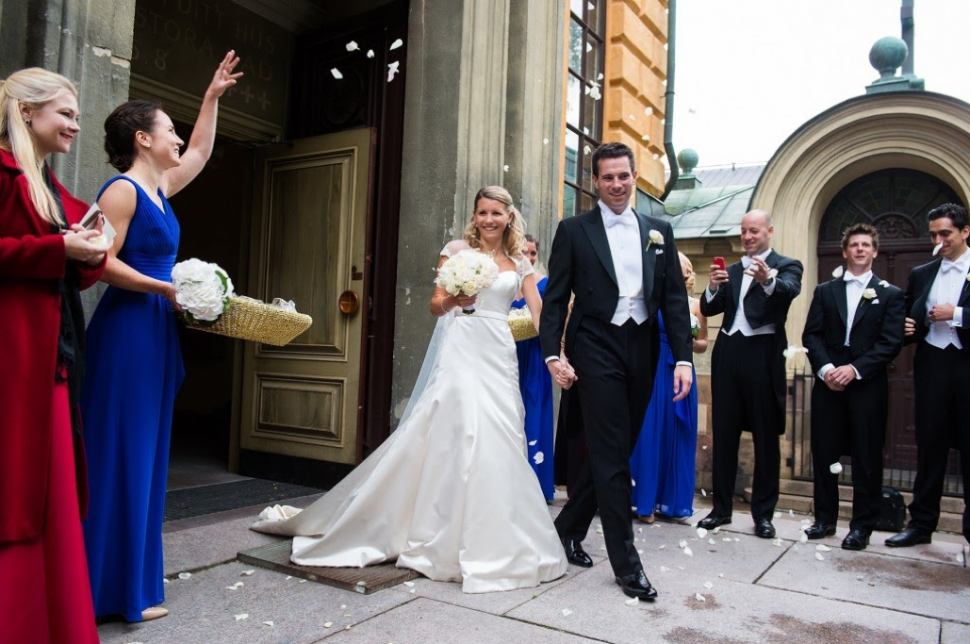 Newlyweds leave a church with groom wearing white tie