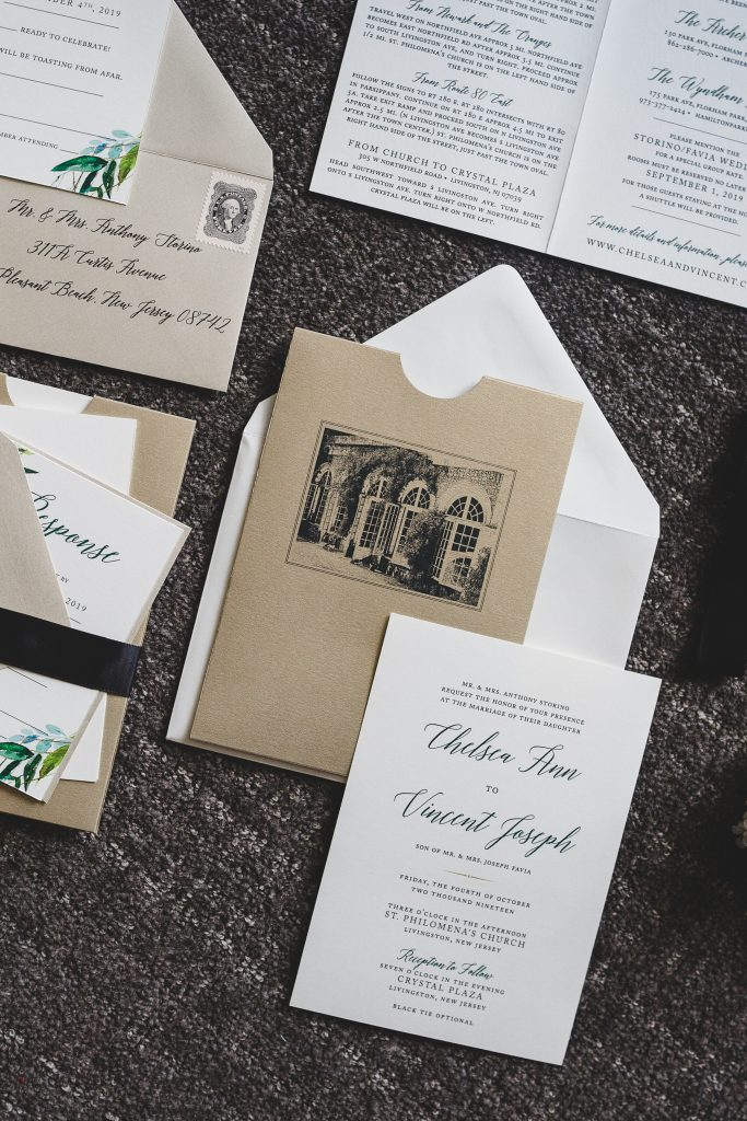 A recycled paper wedding invitation sitting among other wedding papers