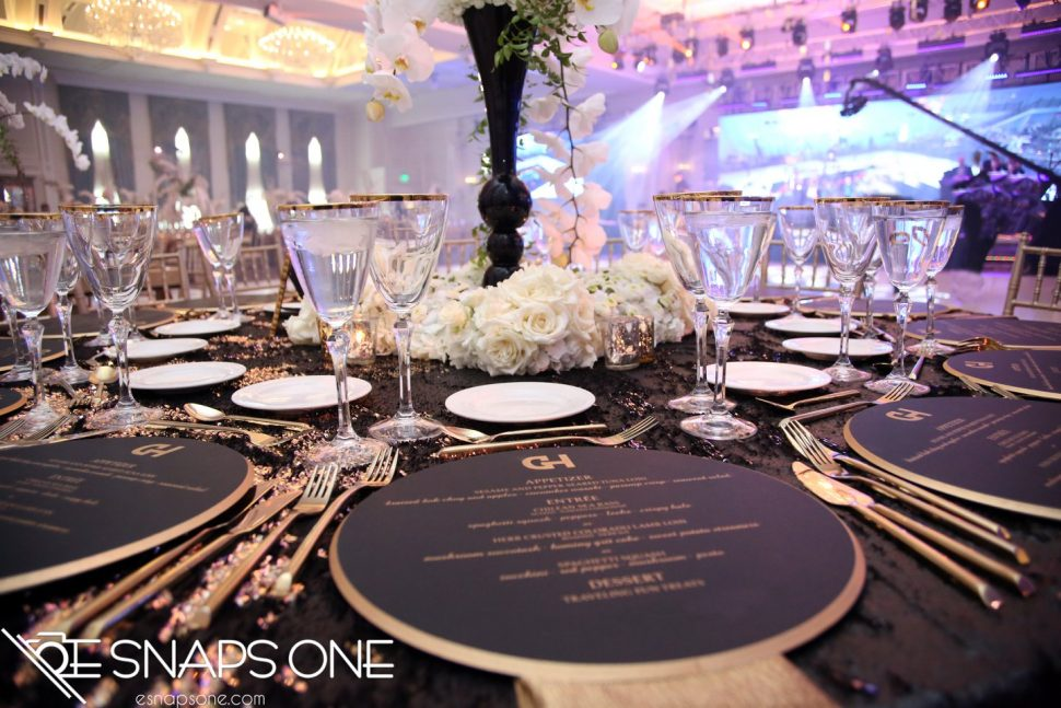 A wedding table setting with the dinner menu at the forefront.