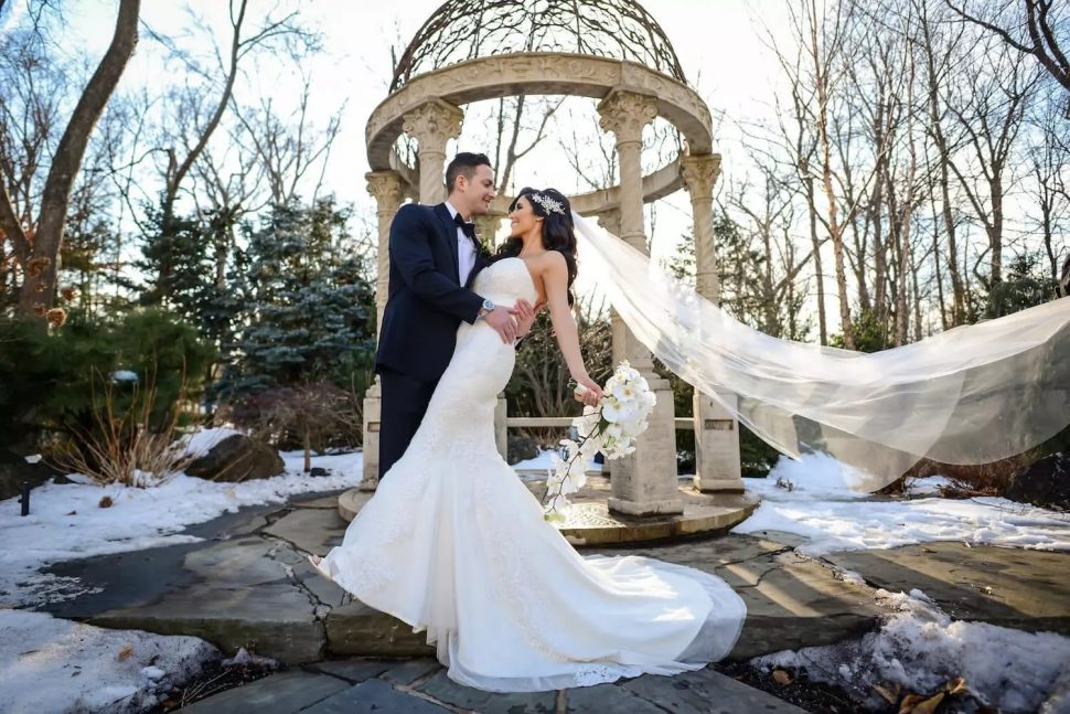 A groom in black tie dips his wife by the outdoor gazebo at The Crystal Plaza in Livingston, New Jersey