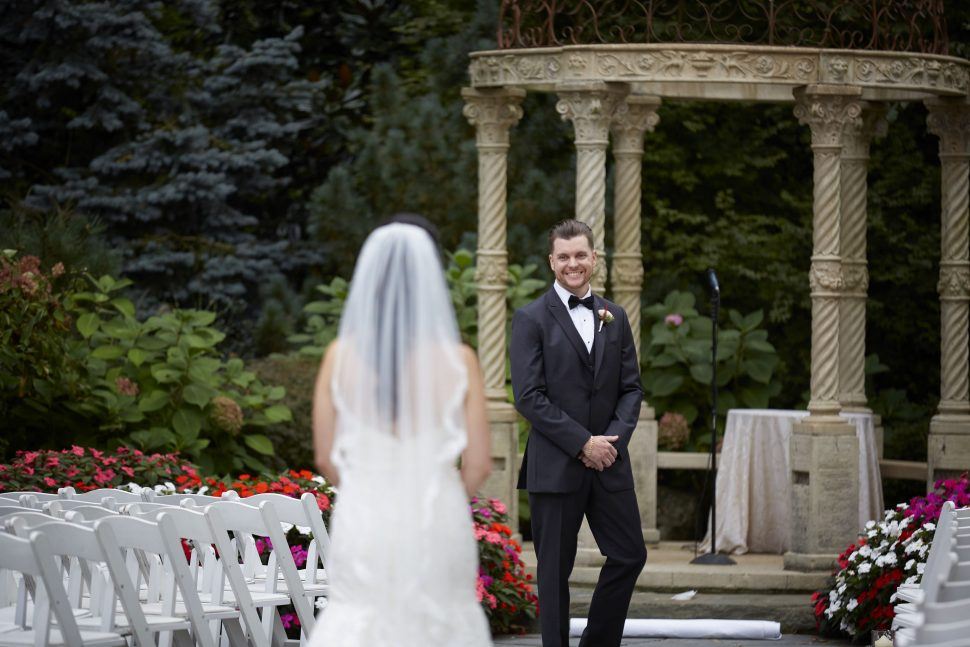 A bride stands in the aisle as her groom sees her for the first time.