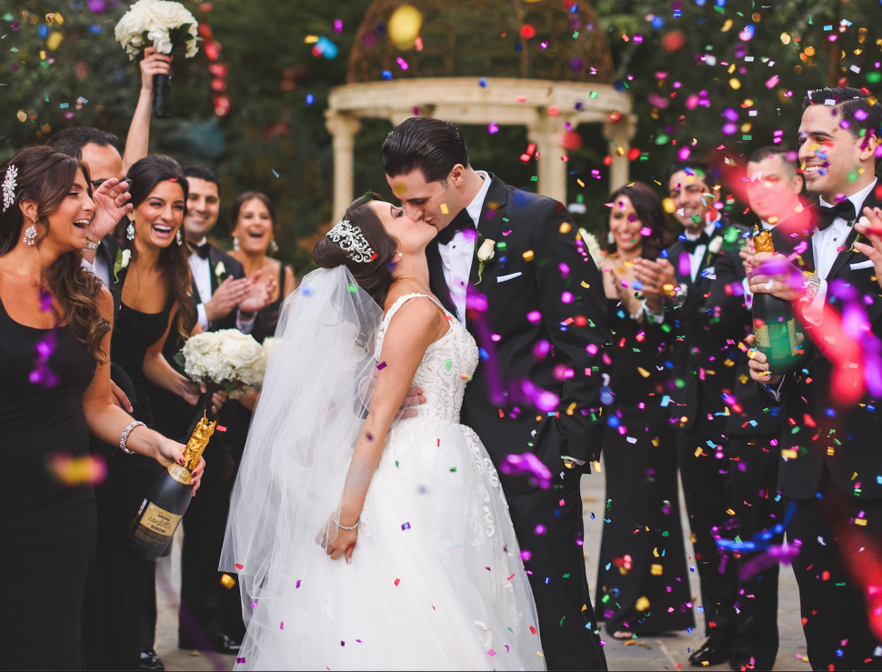 A Bride and groom kiss while the bridal party throws colorful confetti around them.