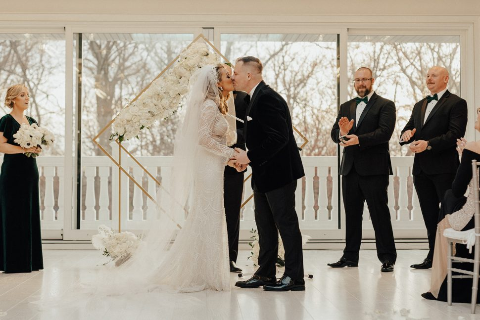 A newly wed couple shares their first kiss as husband and wife.