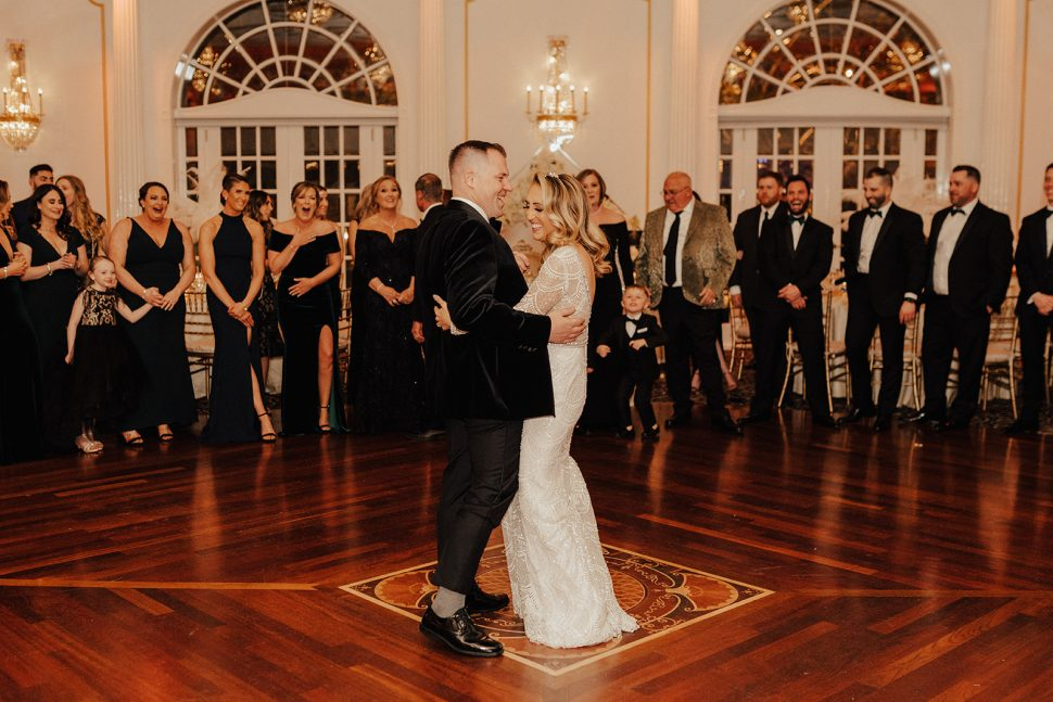 A newlywed couple sharing their first dance in The Crystal Plaza's grand ballroom while guests look on.