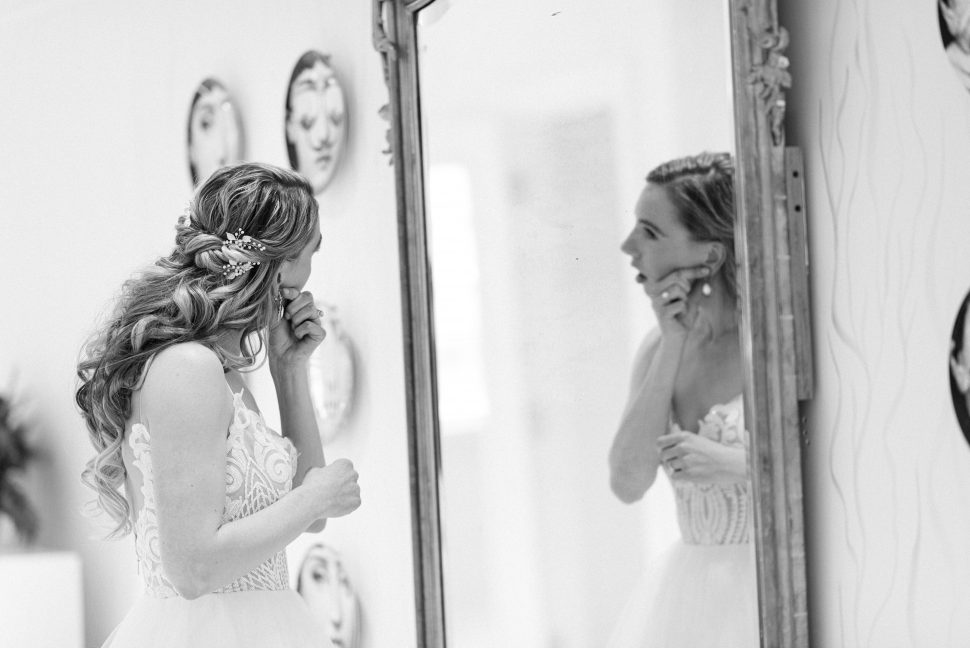 : A bride dressed in a wedding gown looks in a mirror as she puts in her earrings