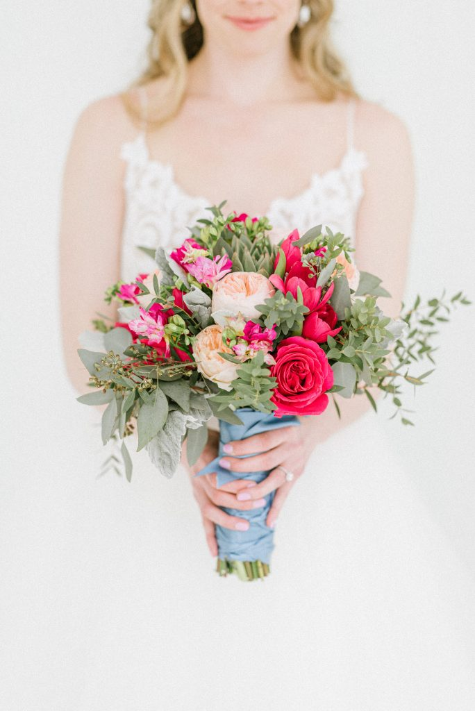 A gorgeous bouquet of wedding flowers wrapped in blue paper