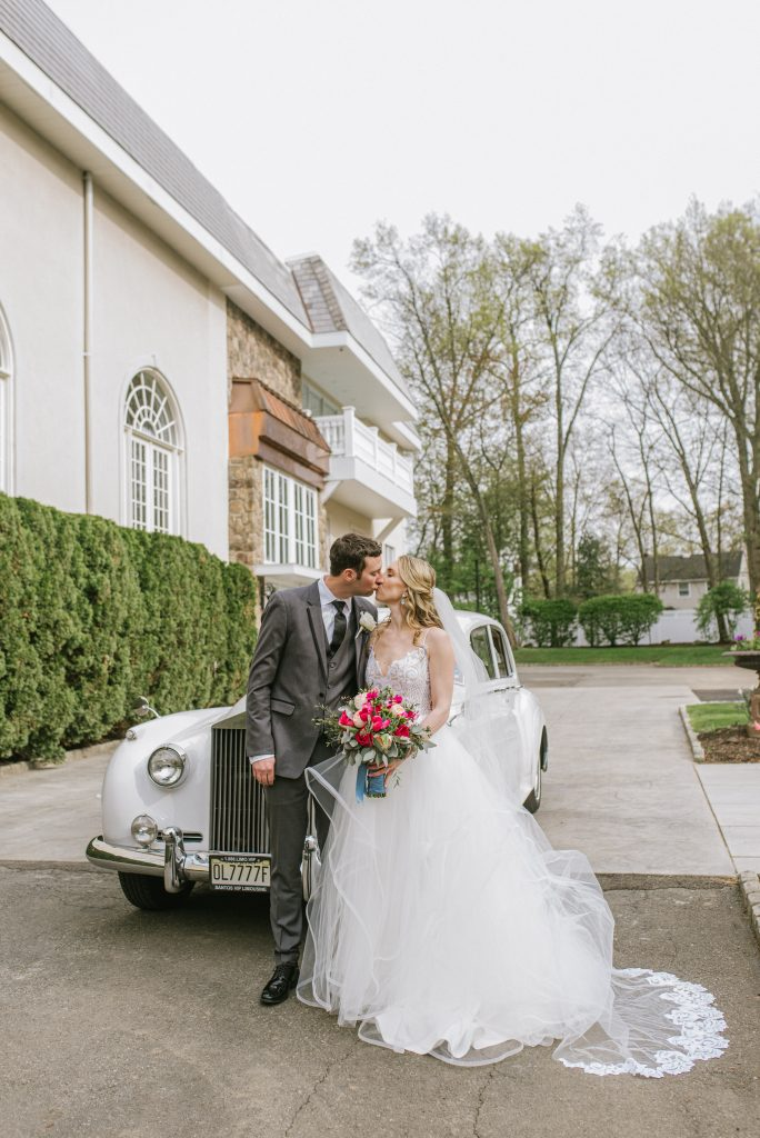 Bride & groom kiss in front of a classic old car