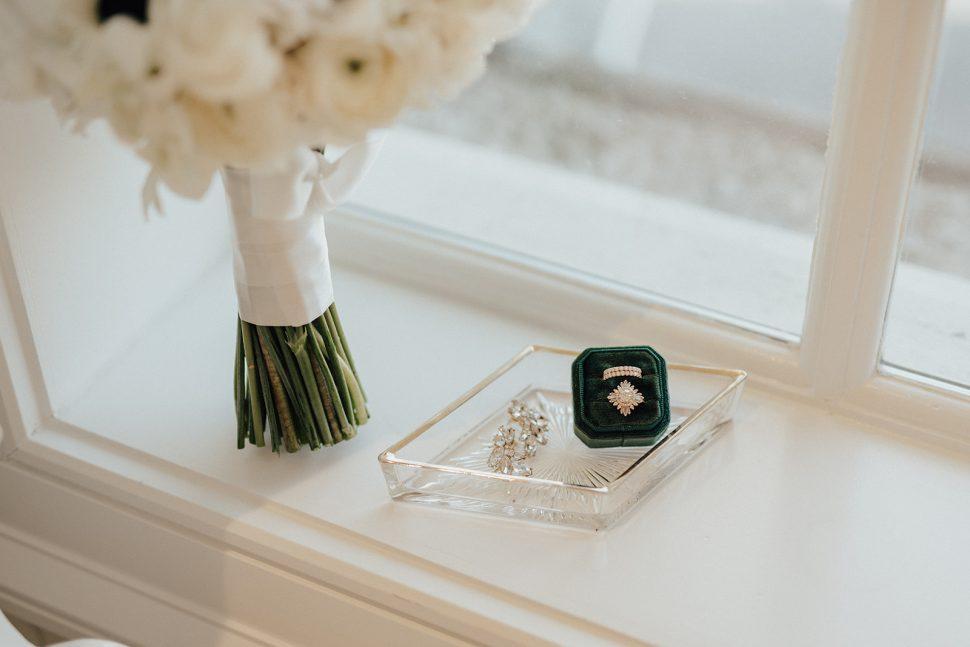 A box of wedding jewelry sitting on a window sill